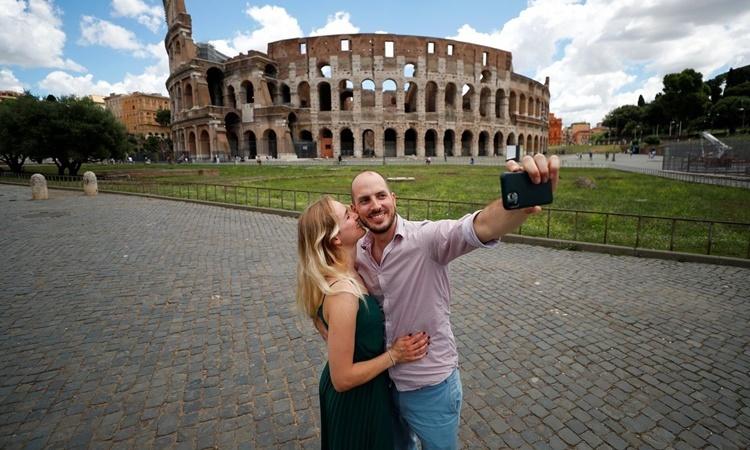 Du khách đến từ Đức chụp hình lưu niệm ở Rome ngày 16/6. Ảnh: Reuters.