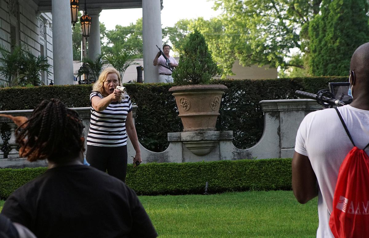 Vợ chồng McCloskey chĩa súng vào đoàn người biểu tình tuần hành qua biệt thự của họ ở thành phố St. Louis, bang Missouri, hôm 28/6. Ảnh: Reuters