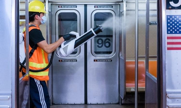 Nhân viên phun thuốc tẩy trùng trên một toa tàu điện ngầm ở New York, Mỹ, ngày 10/6. Ảnh: Bloomberg.