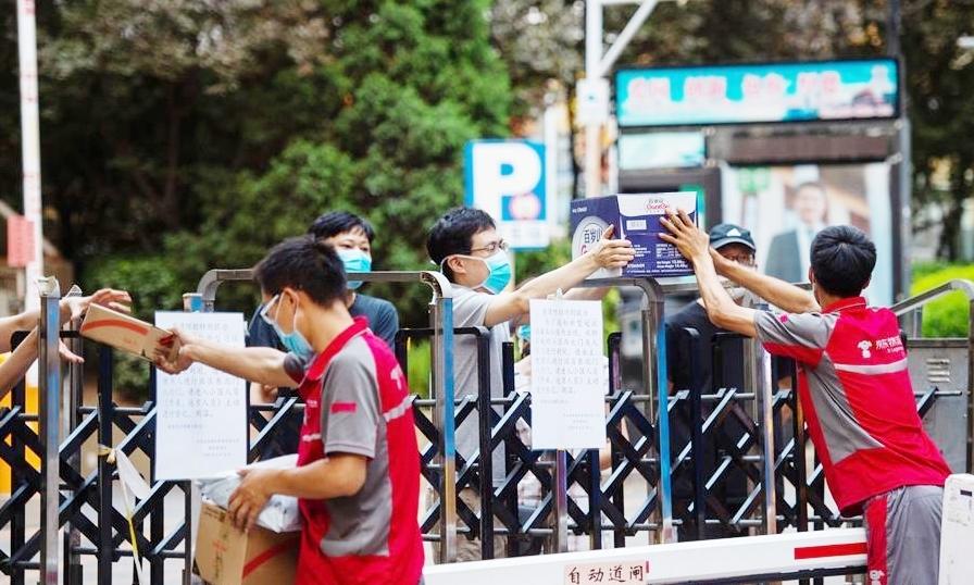 Người giao hàng và người dân trong một khu chung cư ở quận Tây Thành, Bắc Kinh, hôm 17/6. Ảnh: Xinhua.