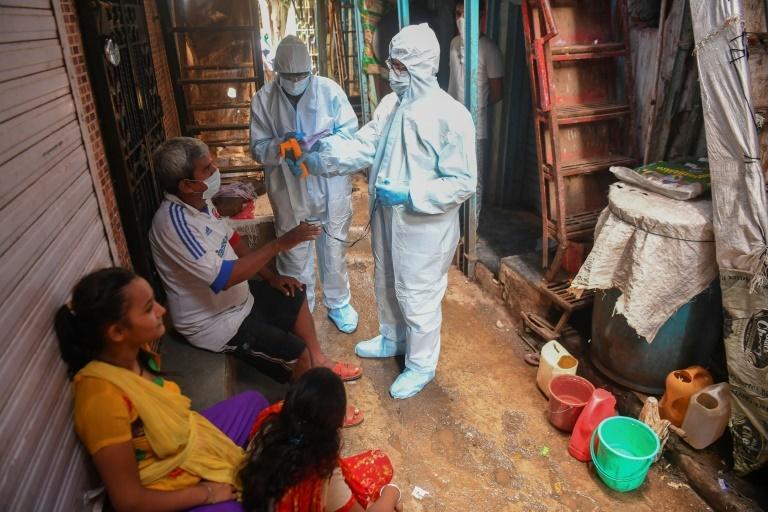 Các nhân viên y tế sàng lọc từng hộ gia đình trong khu ổ chuột Dharavi ở Mumbai hôm 24/6. Ảnh: AFP