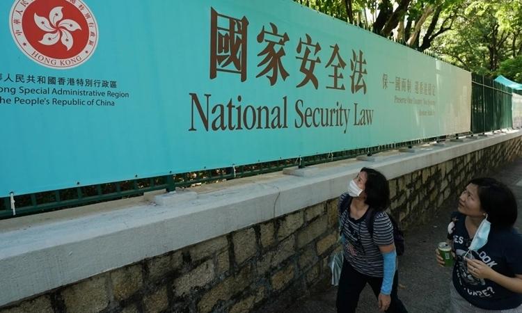 Người dân Hong Kong xem một tấm biển về luật an ninh ngày 30/6. Ảnh: SCMP.