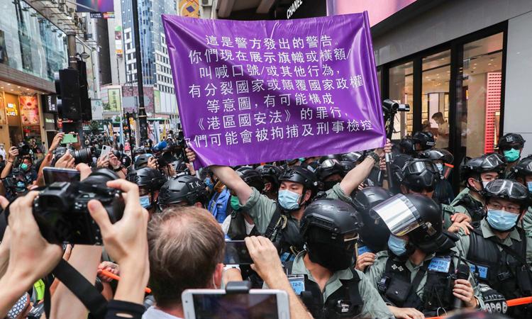 Cảnh sát giơ lá cờ có dòng chữ cảnh báo vi phạm luật an ninh ở Vịnh Causeway hôm nay. Ảnh: SCMP.
