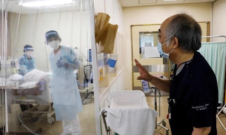 Bác sĩ Yoshihiro Masui nói chuyện với y tá bên trong một phòng chăm sóc đặc biệt. Ảnh: Reuters.