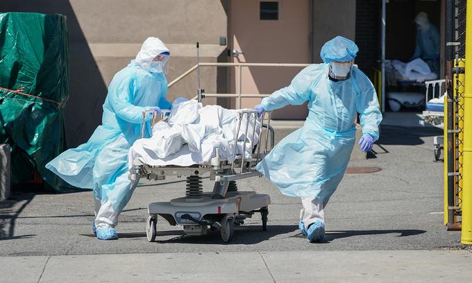 Nhân viên y tế Mỹ chuyển thi thể người chết vì Covid-19 ra xe tải đông lạnh tại bệnh viện ở Brooklyn, New York, hồi tháng 4. Ảnh: AFP.