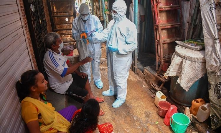 Nhân viên y tế Ấn Độ kiểm tra sức khỏe cho người dân ở khu ở chuột Dharavi, Mumbai, hôm 24/6. Ảnh: AFP.