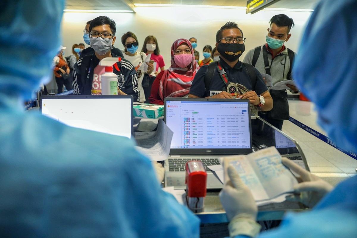 Người nước ngoài thực hiện kiểm tra y tế tại sân bay Tân Sơn Nhất trước khi nhập cảnh hôm 18/3. Ảnh: Hữu Khoa.