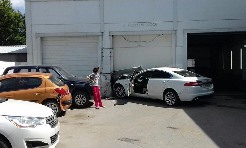 Chiếc Jaguar hư hỏng phần đầu sau cú đâm vào cửa garage. Ôtô màu cam là xe bị đâm trúng vào đuôi và hích sang ôtô màu đen bên cạnh. Ảnh: News Tula