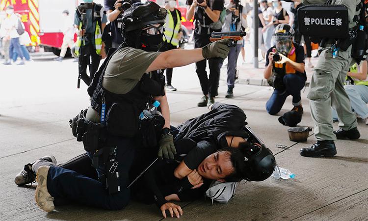 Cảnh sát Hong Kong chĩa súng xịt hơi cay để cảnh báo không lại gần khi bắt một người biểu tình trên phố, ngày 1/7. Ảnh: Reuters.