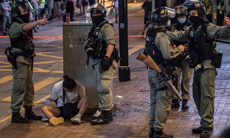 Cảnh sát Hong Kong bắt một người biểu tình (ngồi dưới đất), ngày 1/7. Ảnh: AFP.