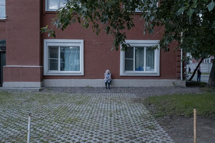 Một phụ nữ ngồi bên ngoài nhà nghỉ của Dom Druzei ở Moskva. Ảnh: Washington Post.