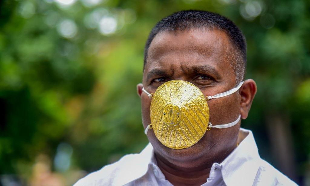 Doanh nhân Shankar Kurhade đeo khẩu trang vàng tại thành phố Pune, Ấn Độ, hôm nay. Ảnh: AFP.