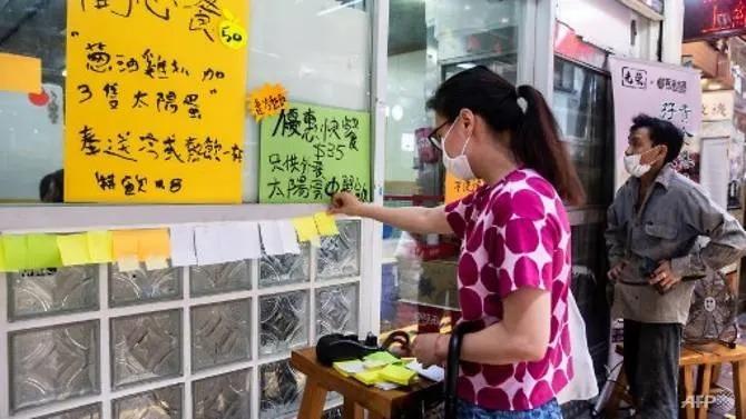 Một phụ nữ dán mảnh giấy ghi chú trống lên tường một nhà hàng ở Hong Kong hôm 3/7. Ảnh: AFP.