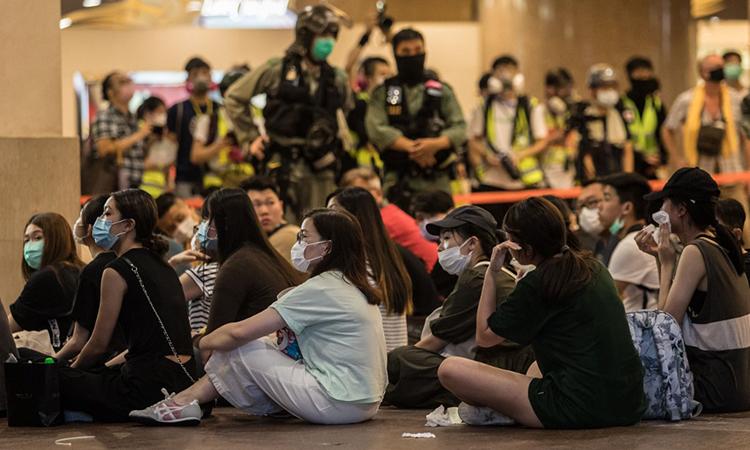 Người biểu tình (ngồi dưới đất) sau khi bị cảnh sát chống bạo động Hong Kong bắt, ngày 1/7. Ảnh: AFP.