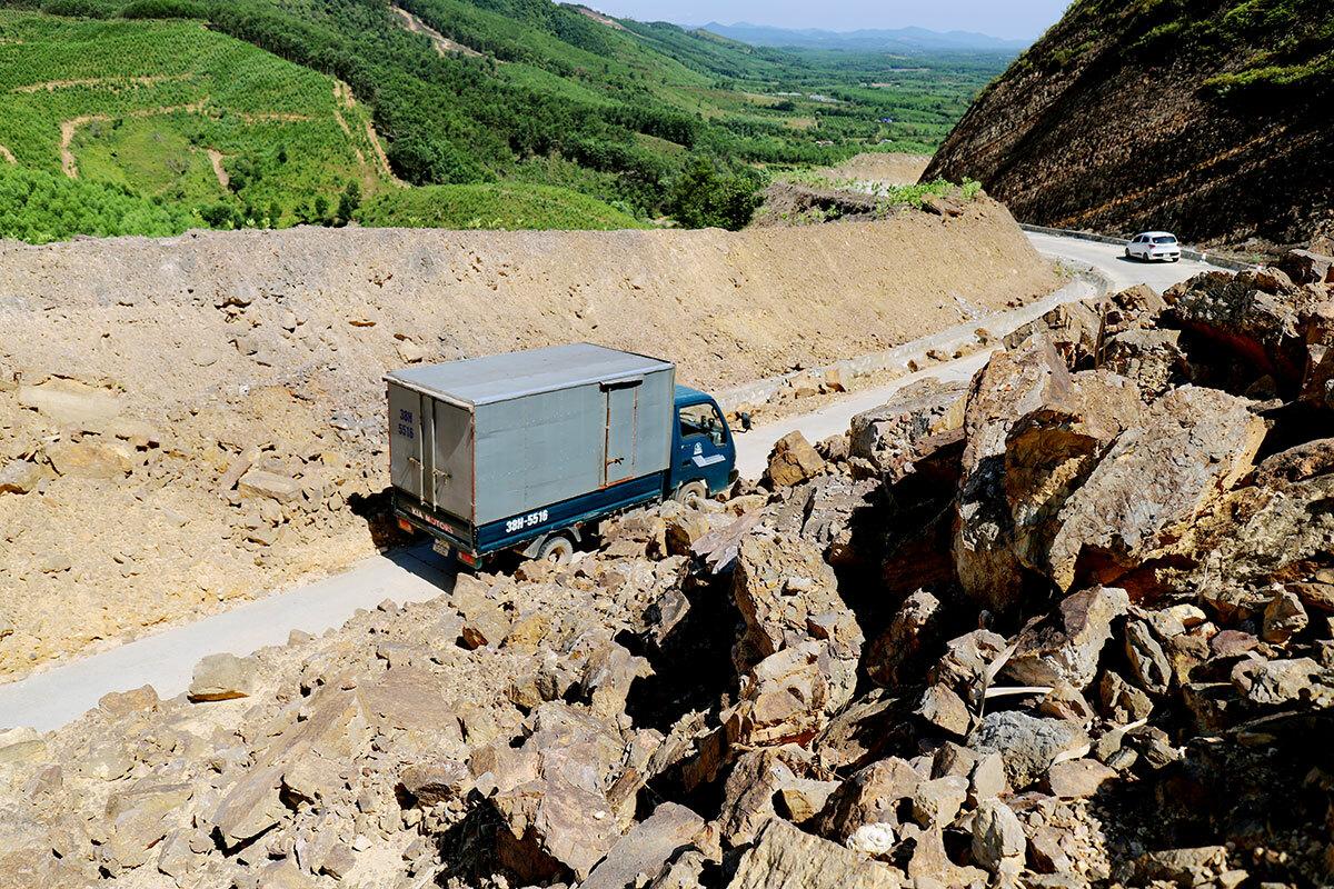 Nhiều điểm sạt lở đất đá tràn xuống lòng đường, chỉ đủ cho một chiếc xe tải nhỏ đi qua. Ảnh: Đức Hùng