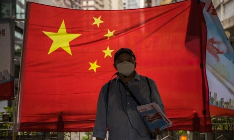 Một người ủng hộ Bắc Kinh phát báo trước cờ Trung Quốc tại Hong Kong ngày 1/7. Ảnh: AFP.