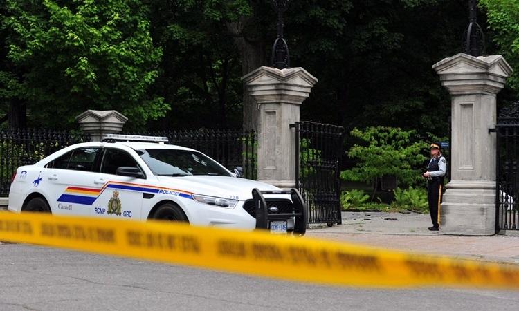 Xe cảnh sát đậu bên ngoài Rideau Hall ở Ottawa, nơi cư trú của Thủ tướng và Toàn quyền, sau khi một người đàn ông vũ trang đâm xe vào cổng. Ảnh: AFP.