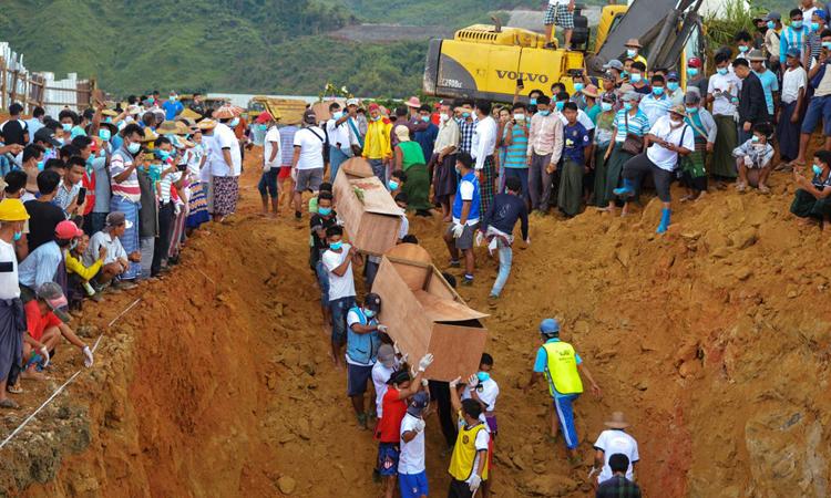 Tình nguyện viên đưa quan tài thợ mỏ thiệt mạng trong vụ lở mỏ ngọc ở bang Kanchin, Myanmar, xuống hố chôn tập thể hôm 3/7. Ảnh: Reuters.