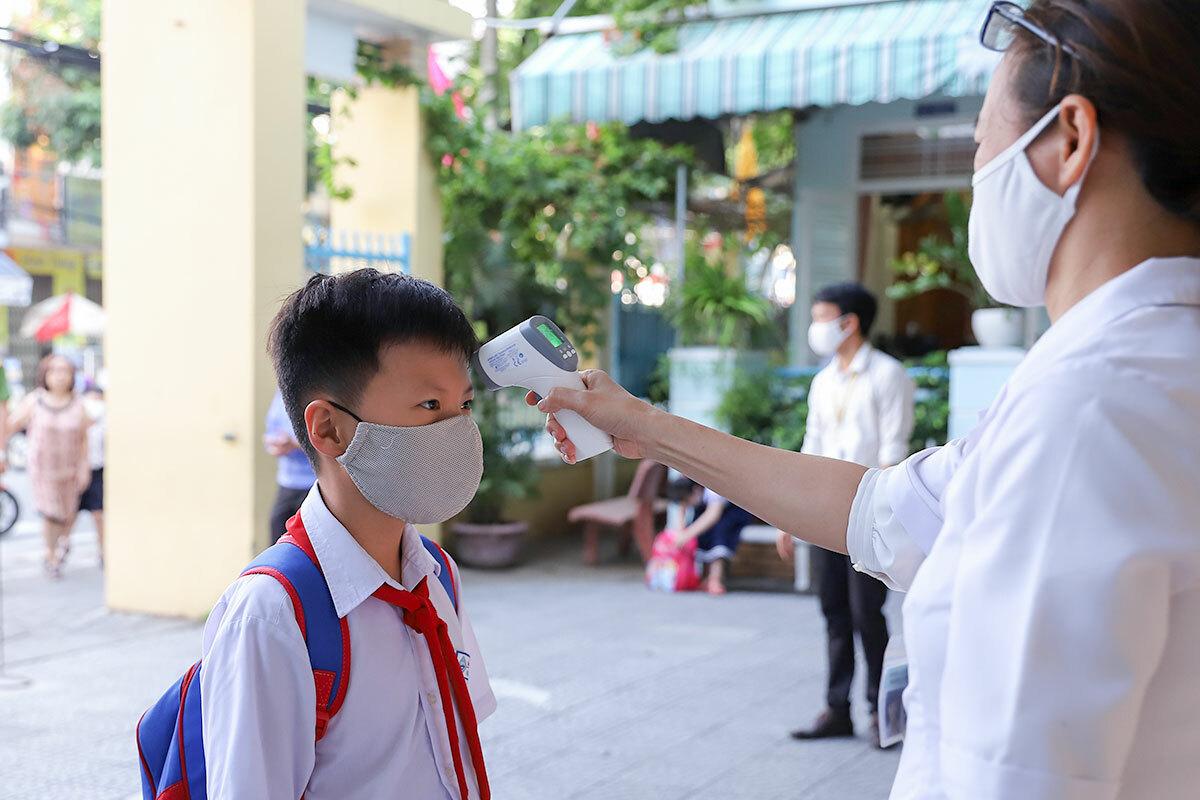 Học sinh ở Đà Nẵng được kiểm tra thân nhiệt, trong lần trở lại lớp học vì nghỉ trách dịch Covid-19, ngày 4/5. Ảnh: Nguyễn Đông.