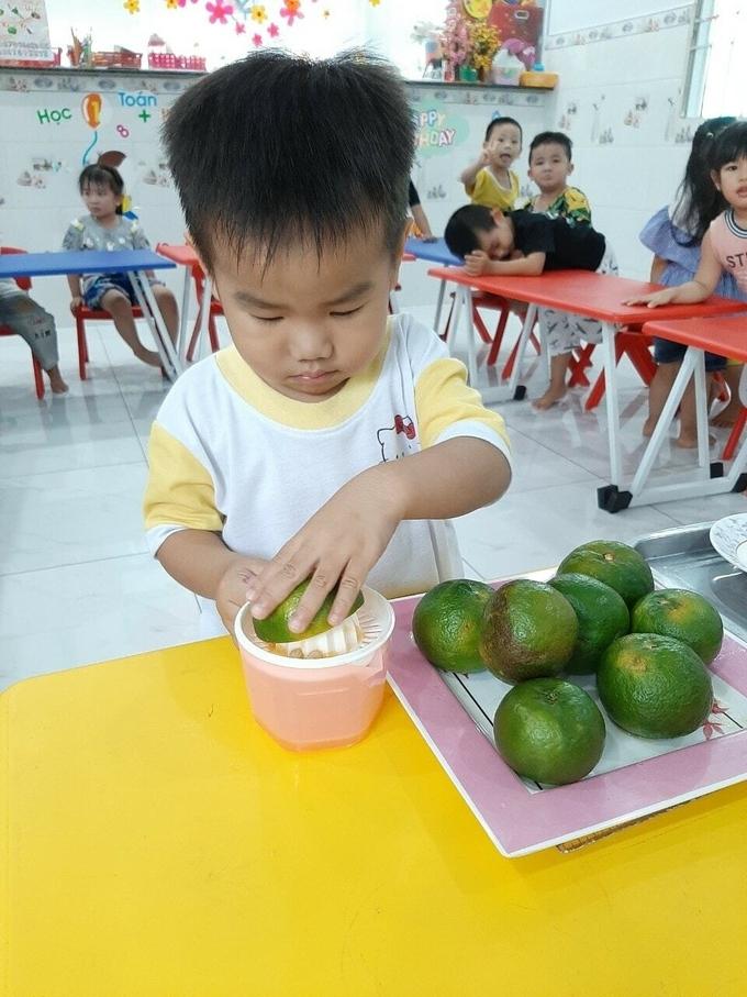 Bé học cách làm nước cam vắt trong tiết học tại trường mầm non.
