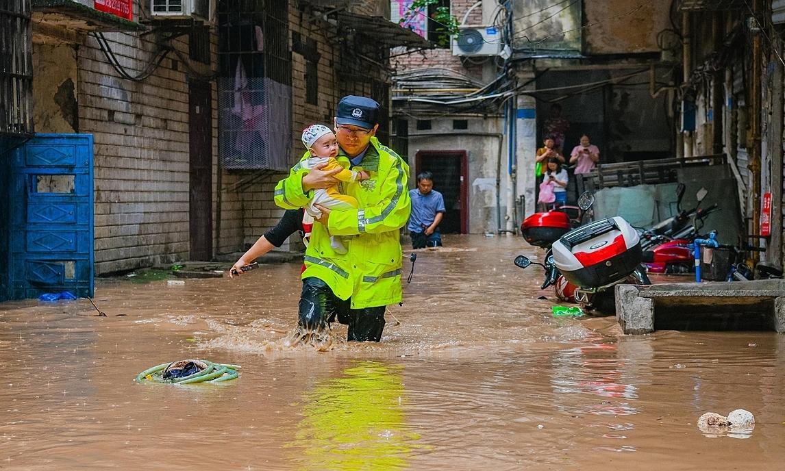 Nhân viên cứu hộ bế một em bé khi mưa lũ tấn công ở quận Kỳ Giang, Trùng Khánh, hôm 22/6. Ảnh: Global Times.
