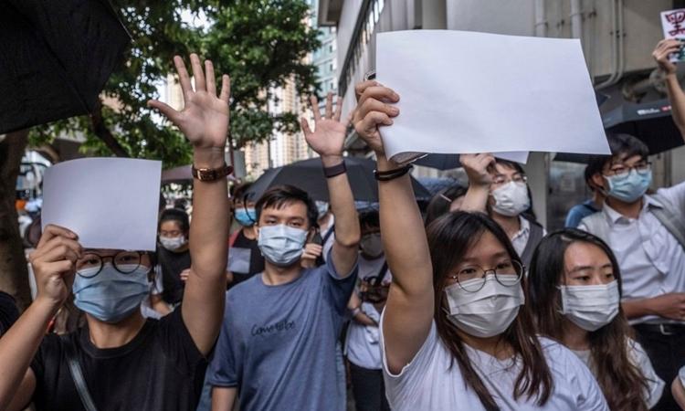 Người biểu tình giơ giấy trắng thay vì biểu ngữ như trước đây để thể hiện sự ủng hộ với những người bị bắt theo luật an ninh mới tại trước một tòa án Hong Kong ngày 3/7. Ảnh: NYTimes.