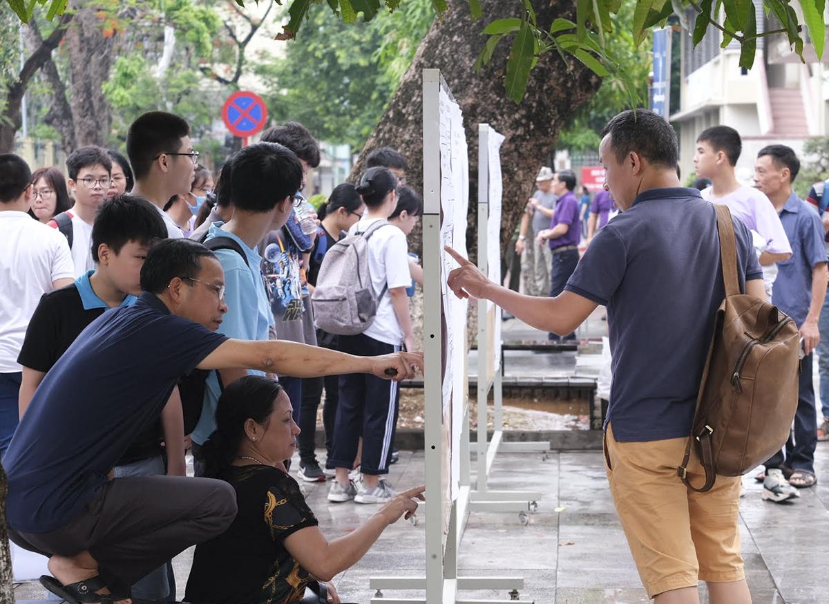 Phụ huynh hỗ trợ con dò phòng thi trong buổi thi vào lớp 10 trường THPT chuyên Ngoại ngữ năm 2020. Ảnh: Dương Tâm.