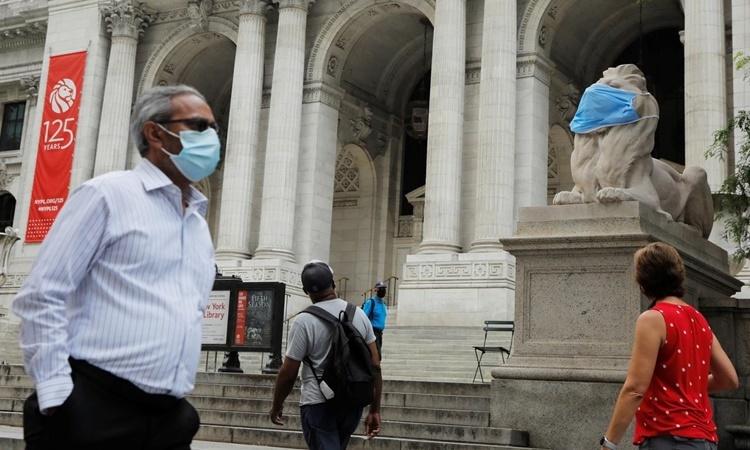 Bức tượng sư tử bên ngoài Thư viện Công cộng New York ở khu Manhattan được đeo khẩu trang hôm 1/7. Ảnh: Reuters.