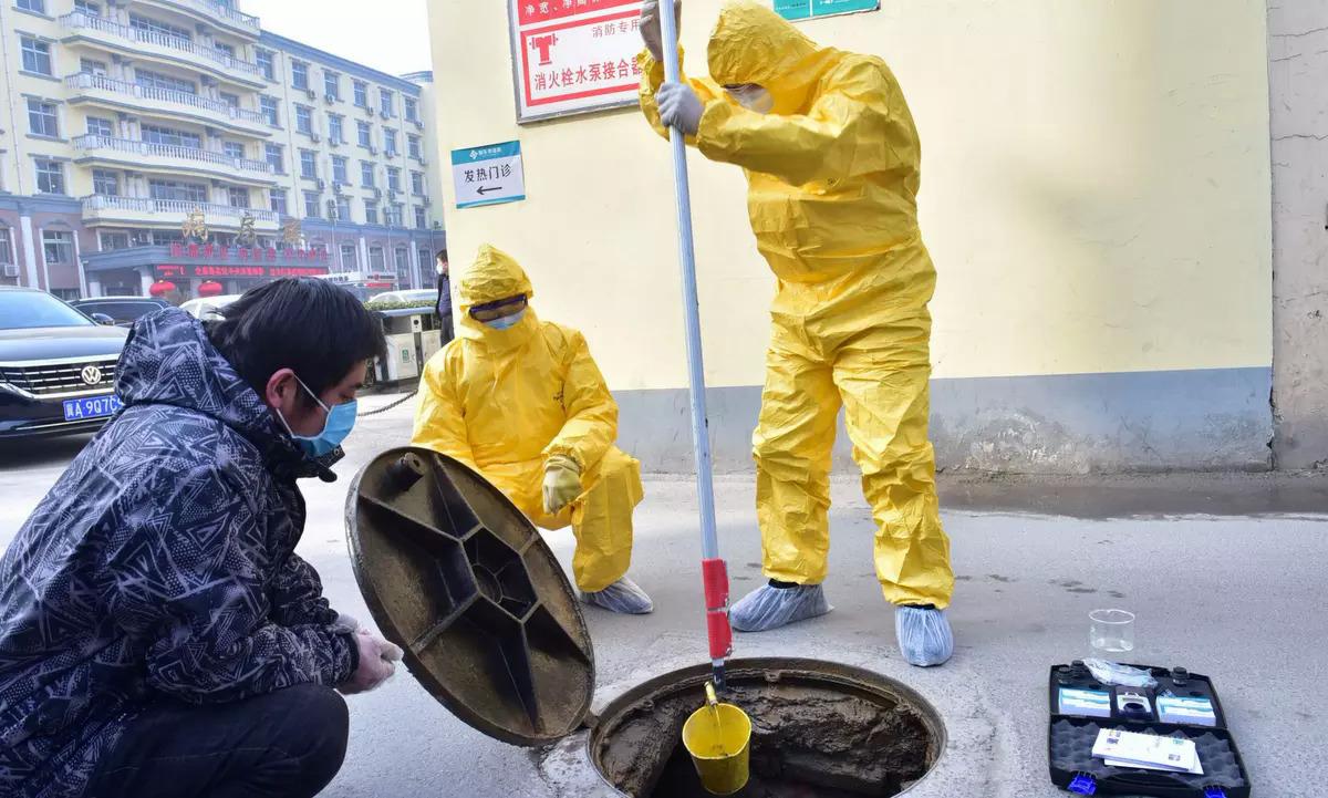 Nhân viên môi trường lấy mẫu nước thải ở một bệnh viện tại tỉnh Hồ Bắc hồi đầu tháng 2. Ảnh: Reuters.
