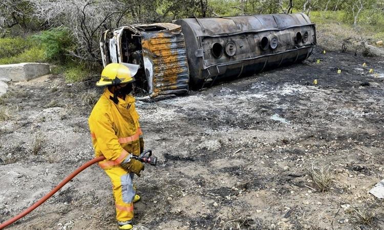 Lính cứu hỏa bên chiếc xe bồn bị thiêu rụi ở thị trấn Pueblo Viejo, Colombia, hôm 6/7. Ảnh: AFP.