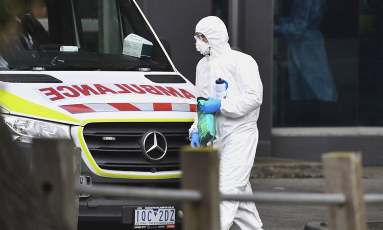 Xe cứu thương đậu bên ngoài một trong 9 tòa nhà công bị phong tỏa do Covid-19 ở Melbourne, Australia hôm 6/7. Ảnh: AFP.