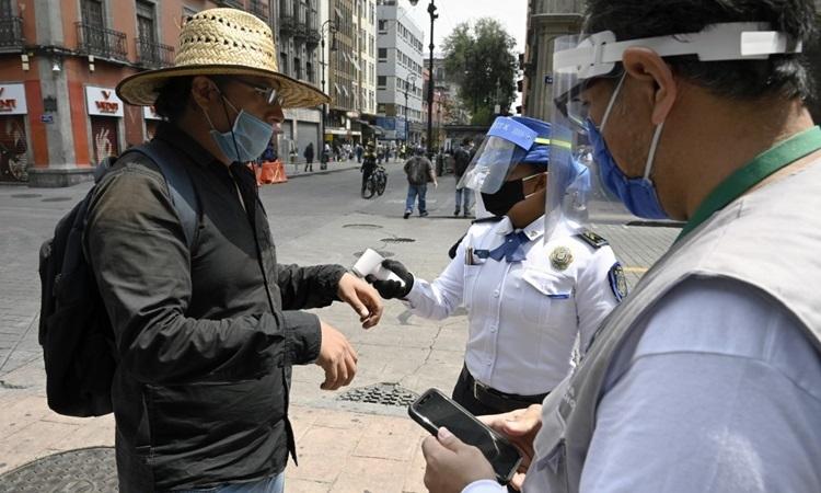 Cảnh sát và nhân viên y tế kiểm tra thân nhiệt của một người qua đường tại thủ đô Mexico City, Mexico hôm 6/7. Ảnh: AFP.