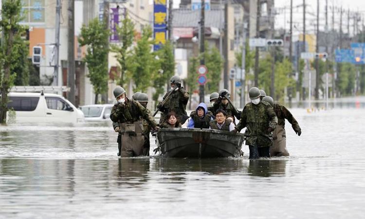 Binh sĩ Lực lượng Phòng vệ Nhật Bản sơ tán người dân tại vùng ngập lũ ở thành phố Omuta, tỉnh Fukuoka hôm nay. Ảnh: Kyodo.