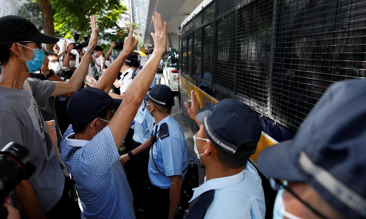 Người ủng hộ đứng cạnh xe chở Tong Ying-kit đến tòa án hôm 6/7. Ảnh: Reuters.