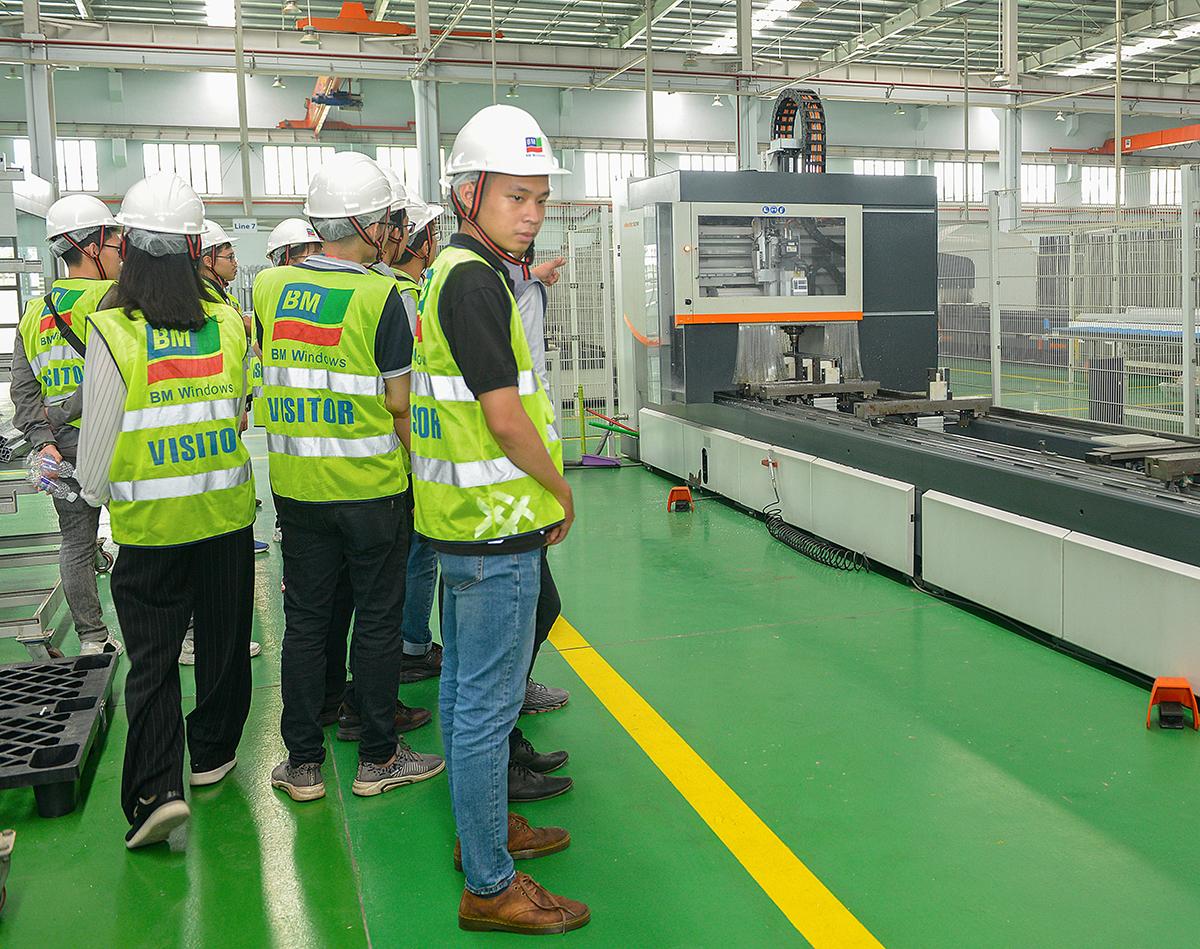 Sinh viên tham quan các máy móc và quan sát quy trình sản xuất sản phẩm nhôm kính, façade.