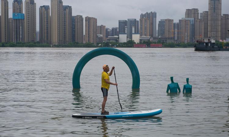 Người đàn ông chèo thuyền cạnh các tác phẩm điêu khắc bị nước lũ nhấn chìm trong công viên gần sông Vũ Xương, thành phố Vũ Hán hôm 5/7. Ảnh: AP.
