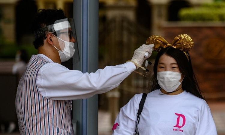 Nhân viên y tế đo thân nhiệt du khách tới công viên Tokyo Disneyland, Nhật Bản, hôm 1/7. Ảnh: AFP.