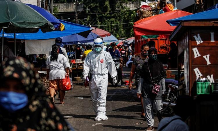 Nhân viên y tế mặc đồ bảo hộ đi qua một chợ truyền thống ở Jakarta, Indonesia để thu thập mẫu xét nghiệm Covid-19 từ các tiểu thương hôm 25/6. Ảnh: Reuters.