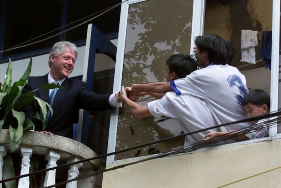 Tổng thống Mỹ Bill Clinton (trái) bắt tay người dân Việt Nam từ ban công một tòa nhà đối diện Văn Miếu - Quốc Tử Giám, Hà Nội tháng 11/2000. Ảnh: AP.