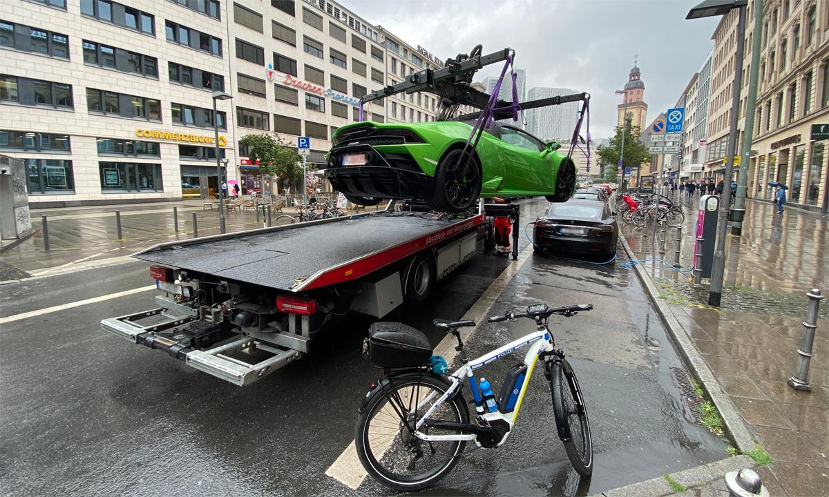 Siêu xe Lamborghini bị cẩu khỏi chỗ đỗ vi phạm. Phía trước là một ôtô điện Tesla đang cắm sạc, và phía sau là xe đạp điện của cảnh sát. Ảnh: Polizei Frankfurt