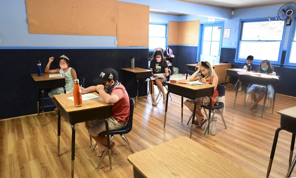 Trẻ em đeo khẩu trang và ngồi học cách xa nhau tại trường Happy Day ở Monterey Park, California hôm 9/7. Ảnh: AFP