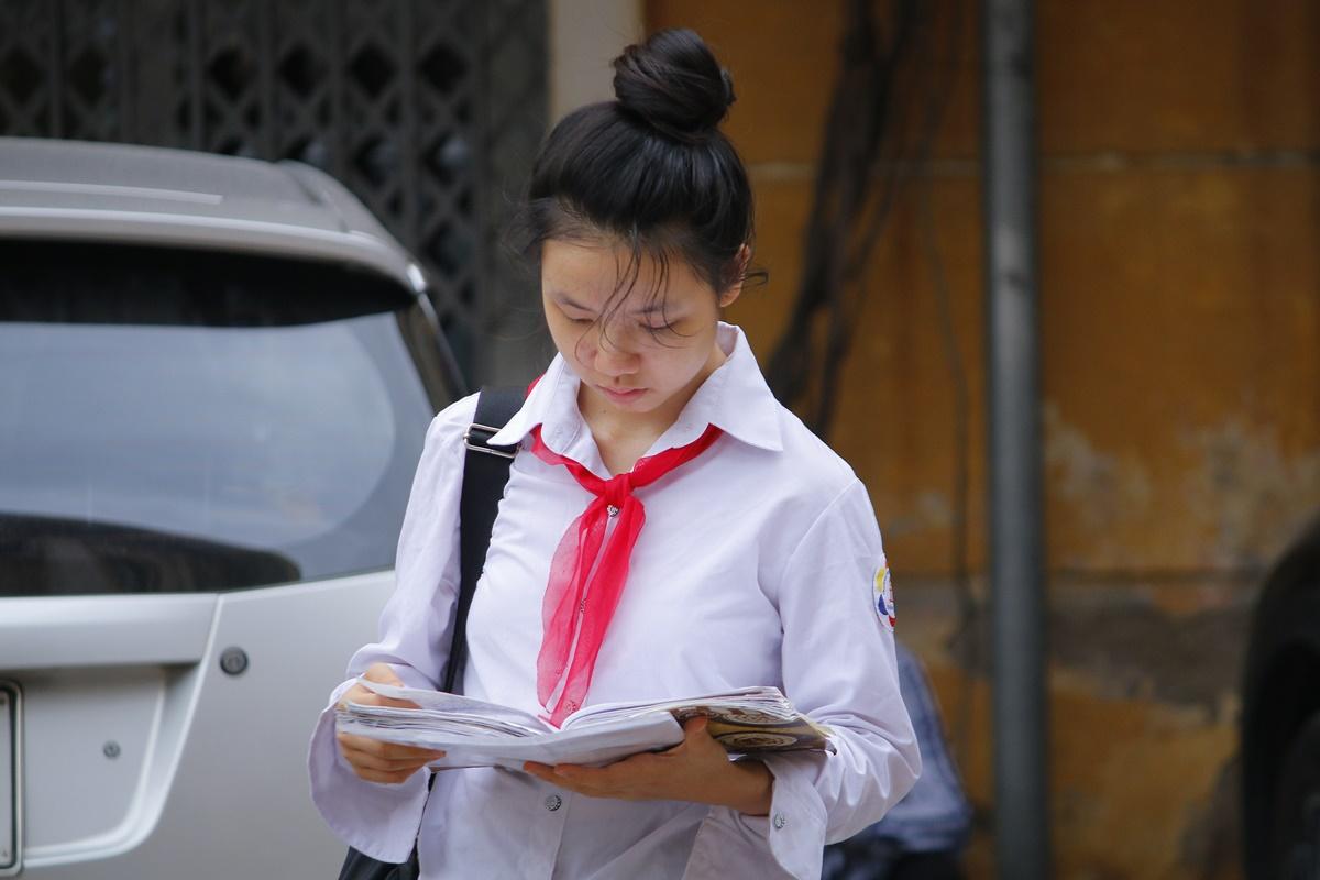 Một học sinh tranh thủ ôn lại bài trước khi thi môn Ngữ văn chung, kỳ thi tuyển sinh vào lớp 10 của trường THPT chuyên Khoa học Xã hội và Nhân văn. Ảnh: Thanh Hằng