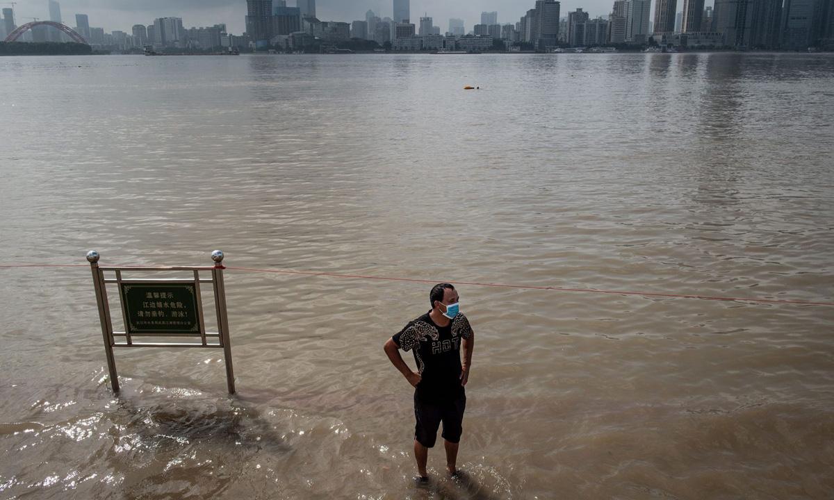 Một người đứng giữa con đường ven sông ngập nước tại thành phố Vũ Hán, tỉnh Hồ Bắc, Trung Quốc, hôm 6/6. Ảnh: Reuters.