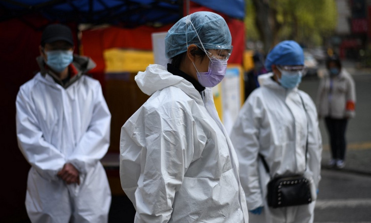 Nhân viên y tế mặc niệm nạn nhân Covid-19 tại Vũ Hán hồi đầu tháng 4. Ảnh: AFP.