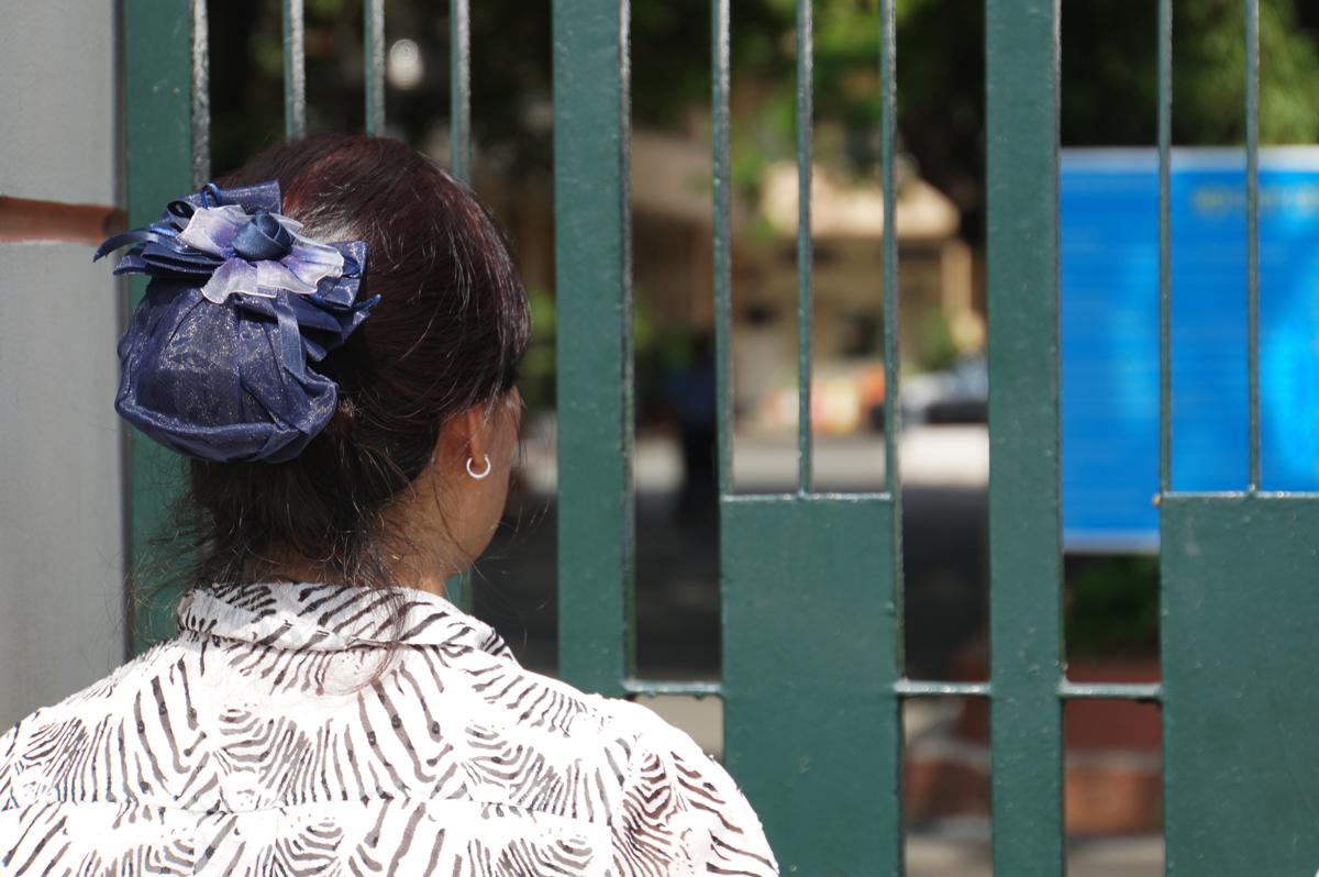 Một người mẹ ngóng con sau giờ thi Toán vào trường Phổ thông Năng khiếu trưa 11/7. Ảnh: Mạnh Tùng.