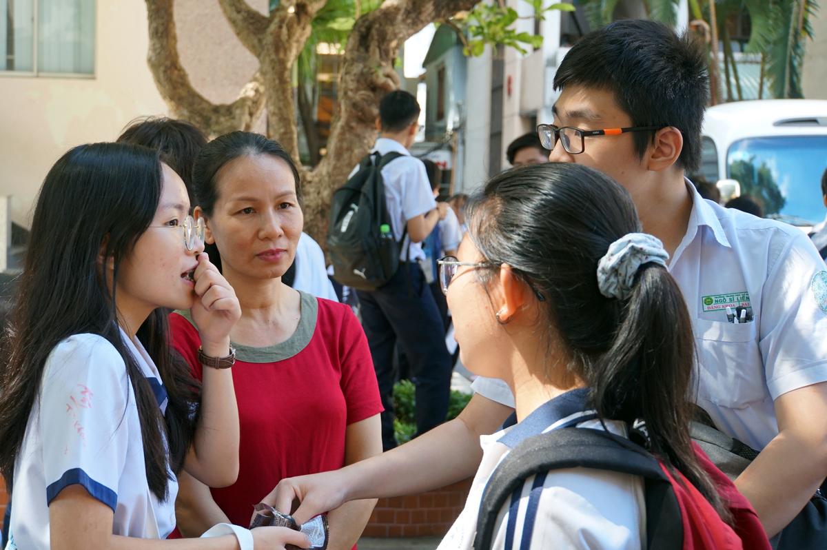 Một phụ huynh (áo đỏ) nghe con và bạn bè trao đổi sau giờ thi môn Văn trường Phổ thộng Năng khiếu, ngày 12/7. Ảnh: Mạnh Tùng.