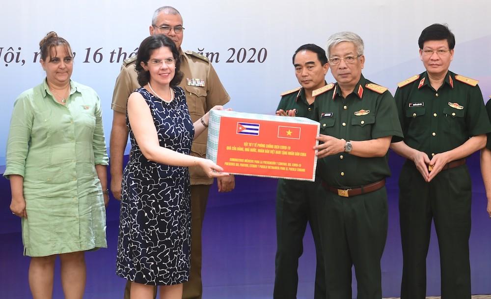 Thượng tướng Nguyễn Chí Vịnh, Thứ trưởng Quốc phòng Việt Nam trao tặng vật tư y tế phòng chống Covid-19 cho Đại sứ Cuba tại Việt Nam, bà Lianys Torres Rivera. Ảnh: Hiếu Duy