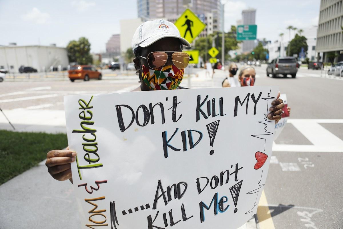 Giáo viên Malikah Armbrister biểu tình cùng các đồng nghiệp trước văn phòng học khu hạt Hillsborough, thành phố Tampa, Florida, hôm 16/7, với biểu ngữ Đừng giết con tôi và đừng giết tôi!. Ảnh: AFP
