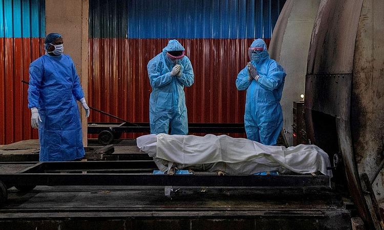 Người nhà bệnh nhân chết vì nCoV cầu nguyện trước lễ hỏa táng ở New Delhi tuần trước. Ảnh: Reuters.