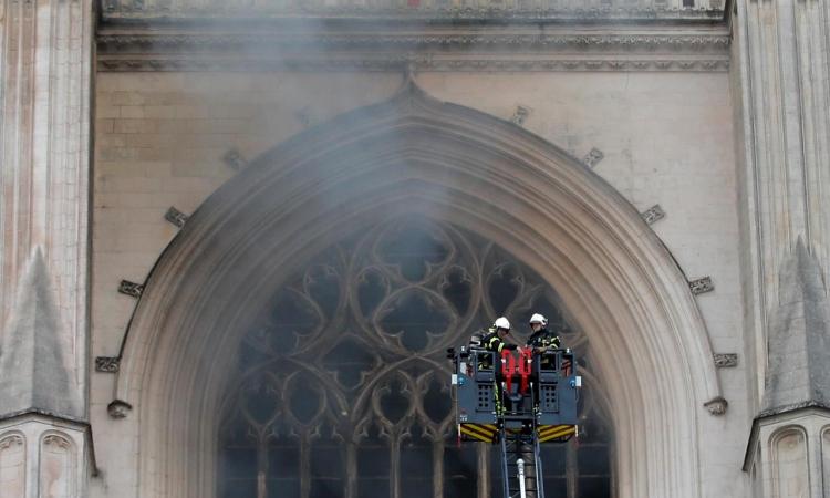 Nhân viên cứu hoả bên ngoài nhà thờ Saint Pierre và Saint Paul tại Nantes, Pháp, hôm 18/7. Ảnh: Reuters.